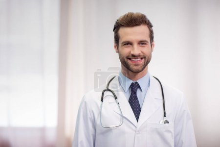 Photo for Young male doctor with stethoscope smiling at camera in hospital - Royalty Free Image