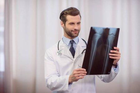 Photo pour Médecin souriant avec stéthoscope tenant et examinant une image radiographique - image libre de droit