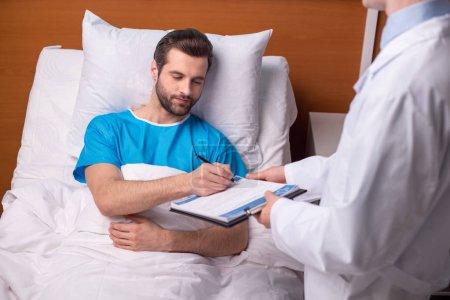 Photo pour Jeune homme malade couché dans un lit d'hôpital et signant un document médical - image libre de droit