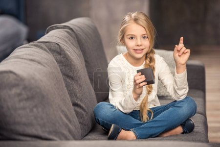 Photo for Cute little girl playing with cube and pointing up with finger - Royalty Free Image