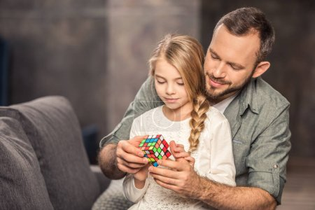 Father and daughter playing with rubik's cube