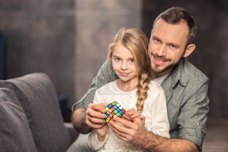Photo for Pensive father and daughter playing with rubik's cube - Royalty Free Image