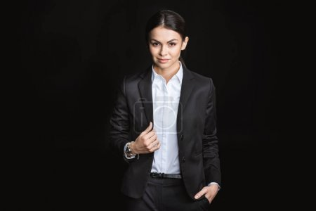 Photo for Attractive young businesswoman in formal wear looking at camera  isolated on black - Royalty Free Image