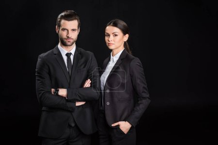 Photo pour Young confident businesspeople in suits looking at camera  isolated on black - image libre de droit