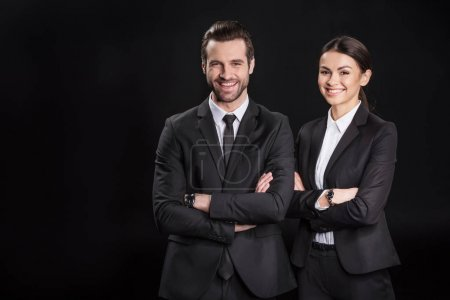 Photo pour Young smiling businesspeople with crossed arms looking at camera  isolated on black - image libre de droit