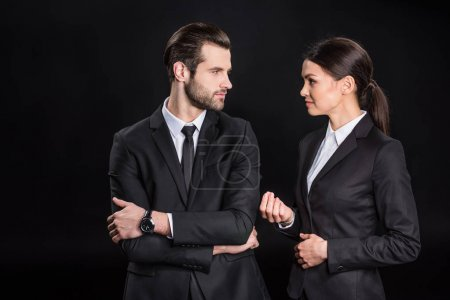 Photo for Young confident businesspeople in formal wear looking at each other isolated on black - Royalty Free Image