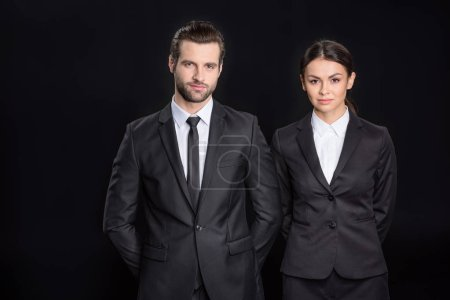 Photo for Young confident businesspeople in formal wear looking at camera  isolated on black - Royalty Free Image