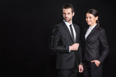 Photo pour Young confident businesspeople standing together and looking away  isolated on black - image libre de droit