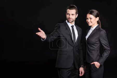 Photo pour Young businessman showing something to smiling businesswoman  isolated on black - image libre de droit
