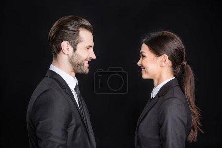 Photo pour Jeune homme d'affaires souriant et femme d'affaires qui se regardent isolés sur noir - image libre de droit