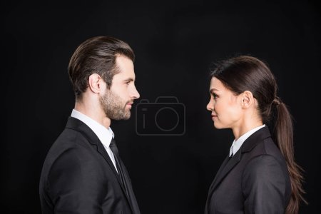 Photo for Side view of businessman and businesswoman looking at each other  isolated on black - Royalty Free Image