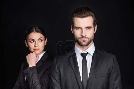 Photo for Young businesswoman with hand on chin looking at confident businessman  isolated on black - Royalty Free Image