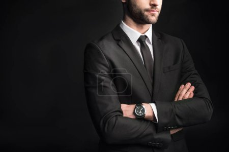 Photo for Midsection view of young confident businessman with arms crossed  isolated on black - Royalty Free Image