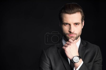 Photo for Young handsome businessman with hand on chin looking at camera  isolated on black - Royalty Free Image