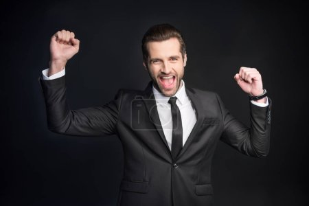Photo for Young handsome businessman triumphing with raised fists  isolated on black - Royalty Free Image