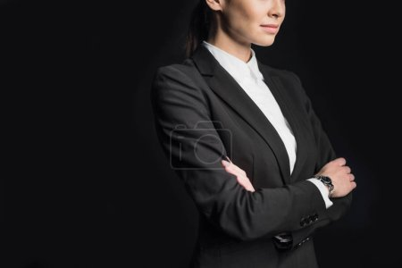 Photo pour Midsection view of young confident businesswoman with arms crossed  isolated on black - image libre de droit