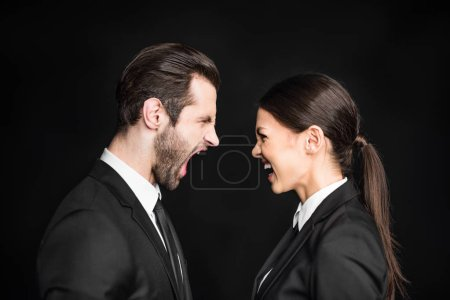 Photo pour Young angry businesspeople screaming at each other  isolated on black - image libre de droit