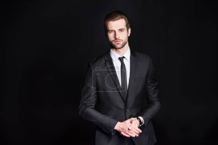 Photo for Young handsome confident businessman looking at camera  isolated on black - Royalty Free Image