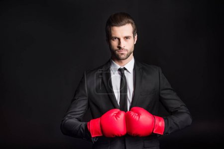 Photo pour Confident young businessman in red boxing gloves looking at camera  isolated on black - image libre de droit