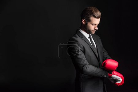 Photo pour Young businessman adjusting red boxing gloves  isolated on black - image libre de droit