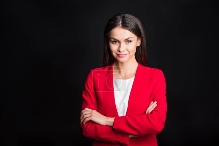Photo for Young attractive businesswoman with arms crossed smiling at camera isolated on black - Royalty Free Image