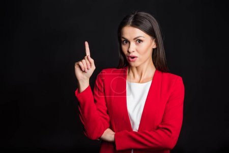 Photo for Young surprised businesswoman pointing up with finger  and looking at camera isolated on black - Royalty Free Image