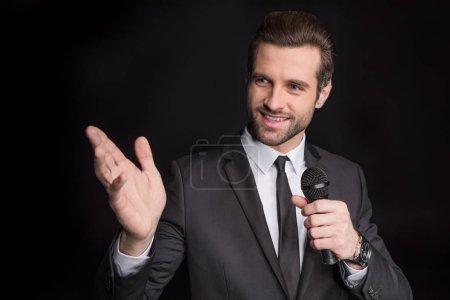 Photo pour Jeune homme amical parlant au microphone et gesticulant isolé sur noir - image libre de droit
