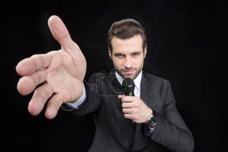 Photo pour Jeune bel homme parlant au microphone et pointant à la main isolé sur noir - image libre de droit