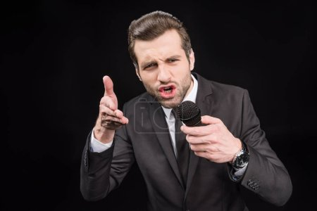 Photo for Young emotional man talking in microphone and gesticulating  isolated on black - Royalty Free Image