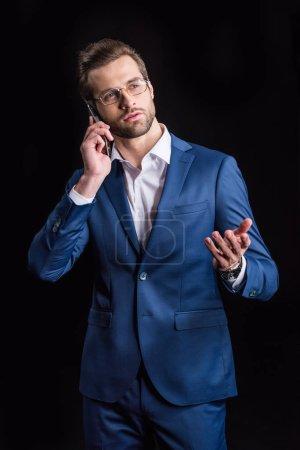 Photo pour Jeune homme d'affaires beau parler sur smartphone et gesticuler isolé sur noir - image libre de droit
