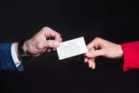 Photo for Close-up partial view of male and female hands holding blank card  isolated on black - Royalty Free Image