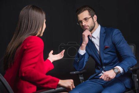 Photo pour Deux jeunes gens d'affaires assis dans des chaises de bureau et bavardant isolés sur noir - image libre de droit