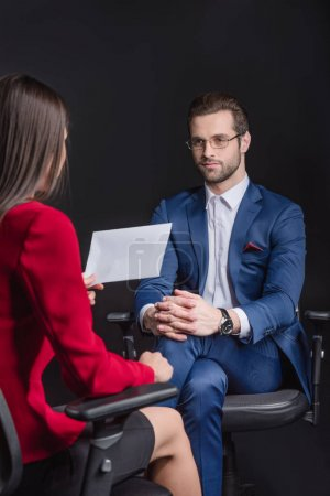 Photo pour Rear view of young businesswoman holding paper and interviewing man  isolated on black - image libre de droit
