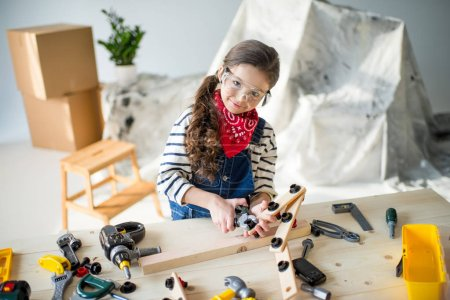 Photo for Adorable little girl in protective goggles playing with toy tools and smiling at camera - Royalty Free Image