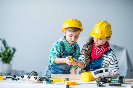 Photo for Little boy and girl in hard hats playing with toy tools in workshop - Royalty Free Image