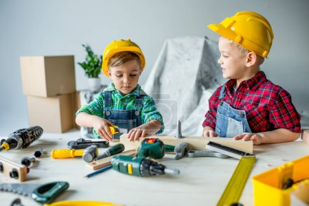 Photo for Cute little boys in hard hats playing with toy tools in workshop - Royalty Free Image