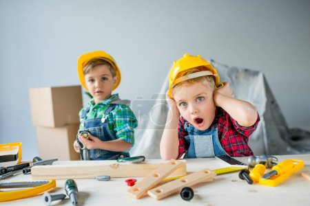 Photo for Shocked little boys in helmets standing at table with toy tools and looking at camera - Royalty Free Image