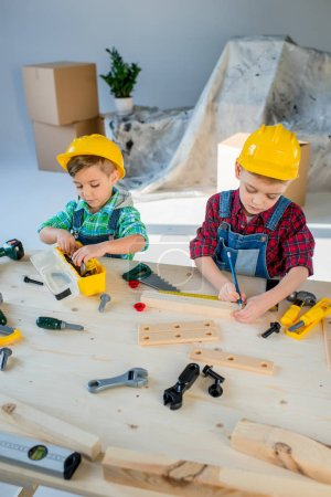 Photo for Two little boys in helmets playing with toy tools in workshop - Royalty Free Image