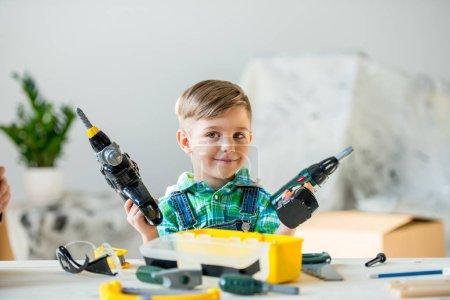 Photo pour Adorable petit garçon tenant des exercices de jouets et souriant dans l'atelier - image libre de droit