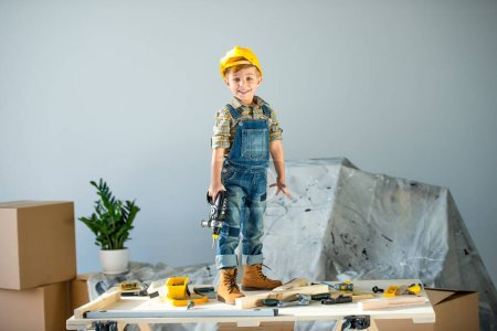 Photo for Smiling little boy in helmet standing on table with toy tools and holding drill - Royalty Free Image