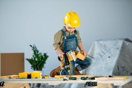 Photo for Cute little boy in helmet and tool belt drilling wooden plank with toy drill - Royalty Free Image