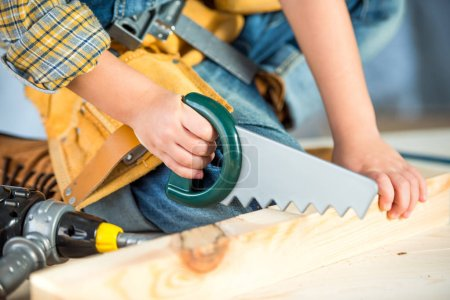 Photo for Close-up partial view of little boy sawing wooden plank with toy saw - Royalty Free Image