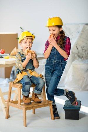 Foto de Lindos niños pequeños en cascos, comer manzana y sandwich en taller - Imagen libre de derechos