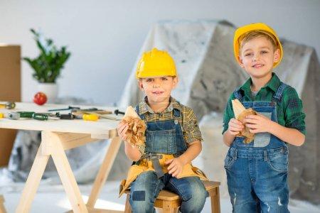 Photo pour Deux garçons mignons dans des casques tenant des sandwichs et souriant à la caméra - image libre de droit
