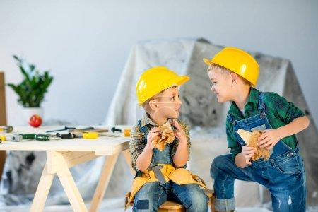 Photo pour Deux garçons mignons dans des casques tenant des sandwichs et se regardant - image libre de droit