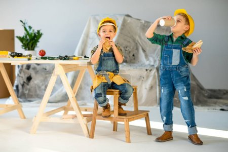 Photo for Two little boys in hard hats and denim overalls eating sandwiches and drinking coffee  in workshop - Royalty Free Image