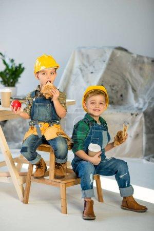 Photo pour Deux petits garçons en casque et salopette en denim mangeant des sandwichs en atelier - image libre de droit