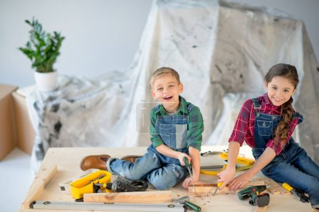 Photo for Little boy and girl sawing woodent plank with toy saw in workhop smiling at camera - Royalty Free Image