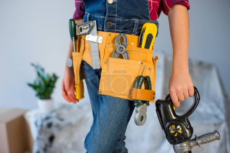 Photo for Midsection view of little  girl in tool belt holding toy drill - Royalty Free Image