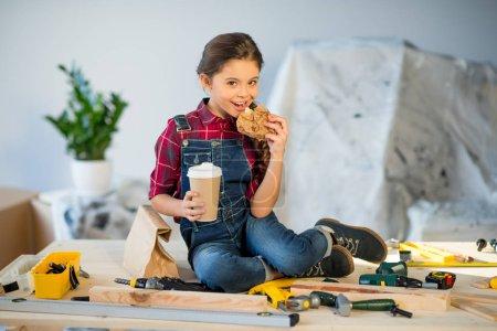 Little girl eating in workshop